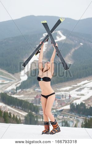 Female Skier Standing On The Top Of The Slope And Holding Skis Above Head. Wearing Swimsuit, Boots.