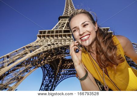 Happy Young Woman Using Cell Phone Against Eiffel Tower, Paris
