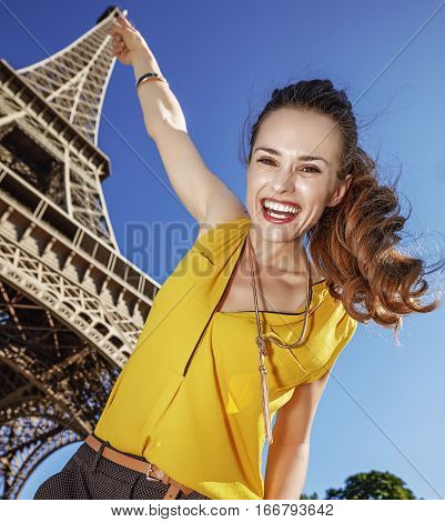 Smiling Woman Pointing On Top Of Eiffel Tower In Paris, France