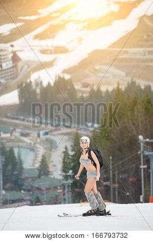 Sexy Beautiful Naked Girl Standing On The Snowy Slope Of The Mountain, Wearing Helmet, Ski, And Back