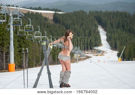 Back View Of Happy Naked Female Skier. Smiling Woman Is Having Fun With Skis On Snowy Slope