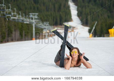 Cheerful Naked Female Skier Is Lying On Snowy Slope Near Ski Lift At  Resort