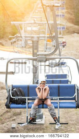 Happy Female Skier Is Sitting On Ski Lift And Riding Up To The Top Of The Mountain With Ski Equipmen