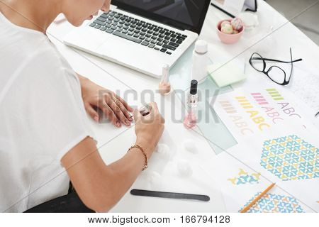 Female designer painting her nails at workplace