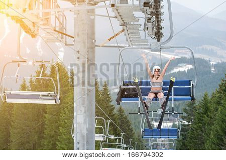 Happy Female Sexy Skier Is Sitting On Ski Lift, Rising Hand Up And Riding Up To The Top Of The Mount
