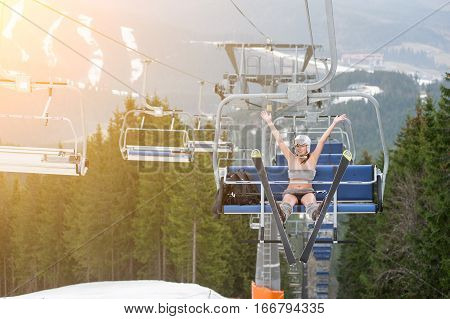 Happy Woman Skier Is Sitting On Ski Lift With Skis, Rising Hand Up And Riding Up To The Top Of The M