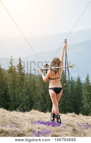 Back View Of Sexy Girl Skier Is Enjoying Warm Spring, Wearing Swimming Suit, Boots And Sunglasses