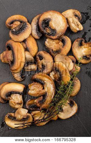 fried mushroom slices and fresh thyme on slate