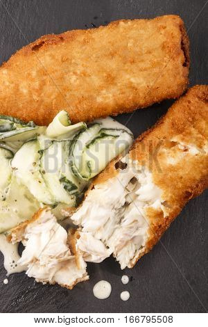 breaded cod and fresh cucumber salad with mixed spice on slate