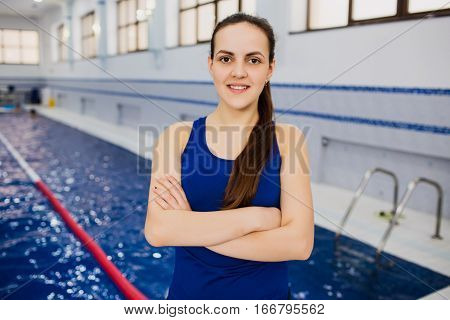 Beautiful young woman swimming trainer, standing with crossed hands looking at camera and smiling. Coach in swimming pool