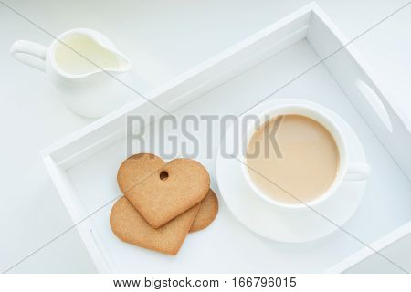 Winter concept. Breakfast. White mug of hot coffee with milk cookies and milk jug in white birchbox. Top view.