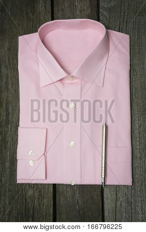 Pink shirt and mobile on wooden background