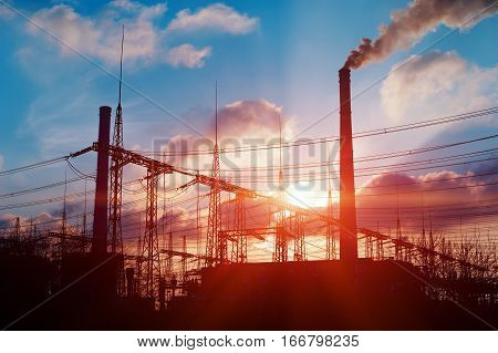 Sun setting over an electrical substation and power plant
