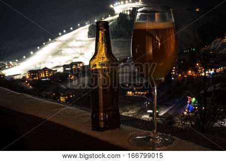 Apres Ski and craft beer concept: Glass and bottle with craft beer on a balcony looking down at a skiing village in Austria