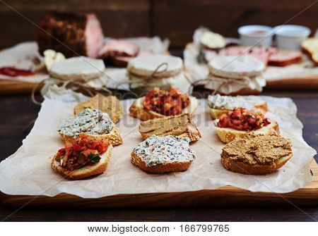 Close-up of gourmet appetizers mix with salad served on a cutting board. . Plate of assorted appetizers with chopped vegetables and ready salads