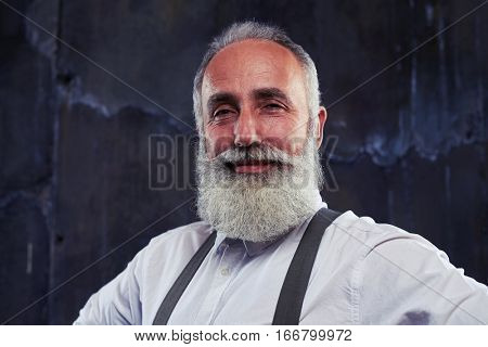 Close-up of senior man getting a good idea. Facial emotions of the bearded man after the moment when he gets a good idea in his mind. He looks excited and turns into hearty laugh