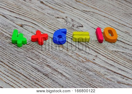 Math example from a colorful plastic numbers on a wooden background. School