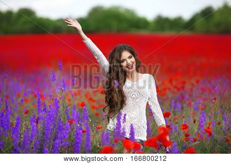 Beautiful Young Woman Portrait In Poppies Field. Attractive Brunette Girl With Long Curly Hair Style