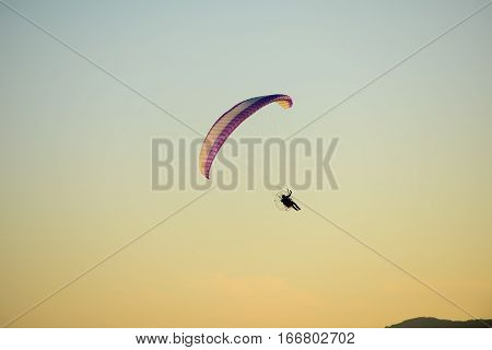paramotor glider flying in the sky over beautiful countryside field landscape at sunset