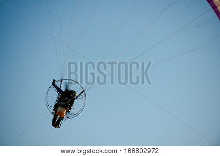 adventure man active extreme sport pilot flying in sky with paramotor engine glider parachute