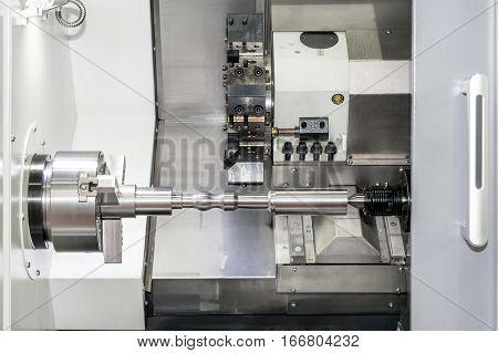 Operator machining automotive part by cnc turning machine.