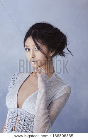 Portrait of futuristic sensual young woman. Beautiful young multi-racial asian caucasian model cyber girl in silver urban clothes with conceptual hairstyle and make-up against blue textured copy-space background. Sci-fi poster style.