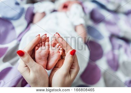 Baby feet in mother and father hands. Tiny Newborn Baby's feet on female Heart Shaped hands closeup. Mom, dad and their Child. Happy Family concept. Beautiful conceptual image of Maternity