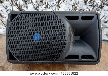 Close-up image of large audio speaker on street stage