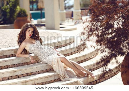 Fashion Elegant Lady In Dress Lying On Steps. Beautiful Young Brunette Woman With Curly Hair And Eve