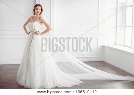 Bride in white dress and long veil indoors. Young gorgeous fashion model posing in white interior studio's room near big window in full lenght