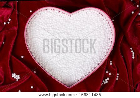 Heart-shaped box filled with small white foam balls on red velvet tablecloth. Top view. Romantic background. Safe packing for fragile items