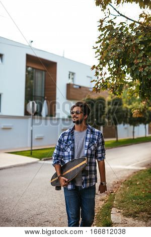 Handsome male carrying longboard on the street.