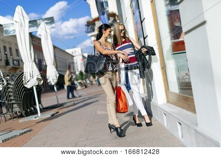 Beautiful cute women shopping spree on street