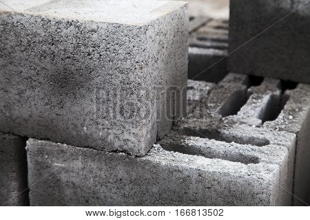 Gray building cinder blocks made of cement stacked close-up. A lot of large concrete bricks stacking texture. Shallow focus