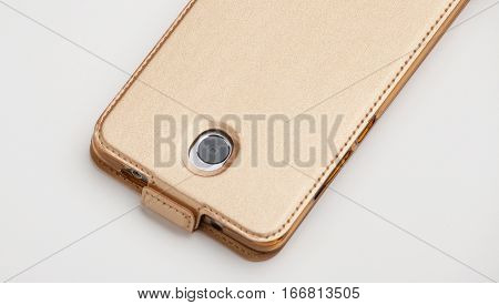 Smartphone in a leather gold cover, back view on white background