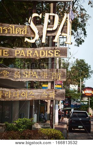 Pattaya Thailand - March 22 2016: Very old wooden sign on a road saying: The Paradise Spa in 4 different languages. Weathered cheap advertisement in Asian resort town