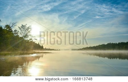 Brilliant and bright mid-summer sunrise on a lake.   Warm water and cooler air at daybreak creates misty fog patches.  Still water along a calm, quiet Ontario lakeside.