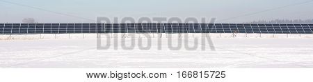 Photovoltaic panels of power station on rural winter snowy field.