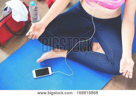 Female fitness and yoga excercise concept with copy space Female listening music from smartphone aafter workout