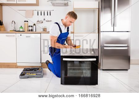 Young Male Technician Checking Oven With Digital Multimeter In Kitchen