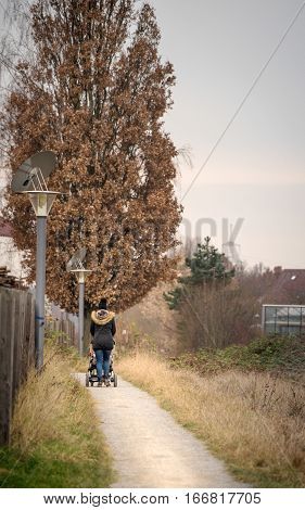 Walking young mother with child buggy in nature