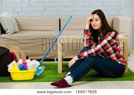 woman dressed in casual clothes sitting on the floor, tired of the household chores. Beside her cleaning supplies, mop for cleaning the house.