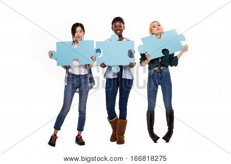 Three Different Ethnic Women Jumping With Puzzle Pieces