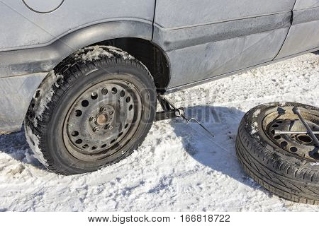 changing a flat tire in the winter snow with backup
