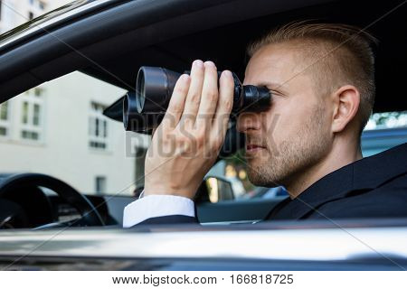Private Detective Sitting Inside Car Looking Through Binocular