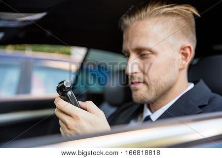 Man Sitting Inside Car Looking At Breathalyzer Test