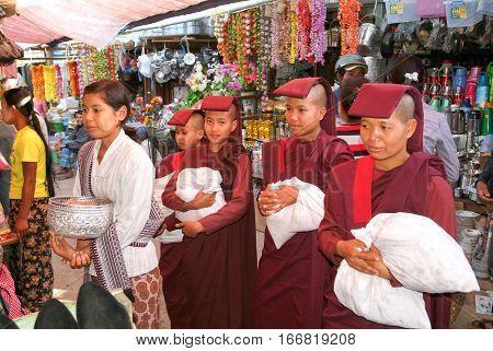 Pyin U Lwin Myanmar - 18 January 2010: Woman with monks asking for offers at the market of Pyin U Lwin on Myanmar