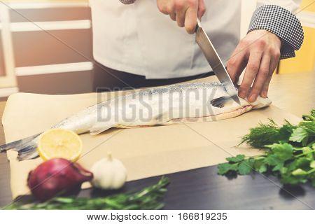 chef cutting salmon fish at restaurant kitchen