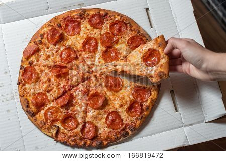 Pizza with salami and cheese. In the hand a slice of pizza
