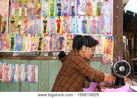 Pyin U Lwin Myanmar - 18 January 2010: Woman working at her sewing-machine at the market in Pyin U Lwin on Myanmar